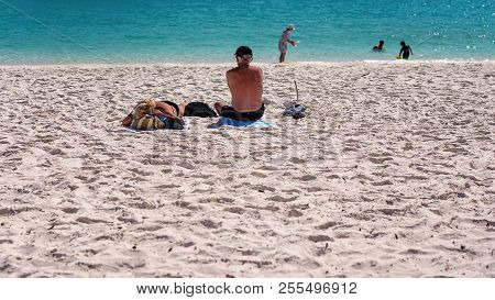 Two Seniors Sunbathing On The White Silica Sand Of Whitehaven Beach In The Whitsunday Islands Austra