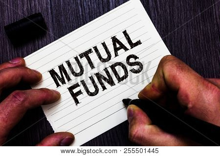Text sign showing Mutual Funds. Conceptual photo An investment program funded by shareholders Individual Stocks Man holding marker notebook page communicate ideas Wooden background. poster
