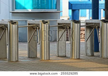 A Row Of Metal Turnstiles On The Sidewalk At The Station