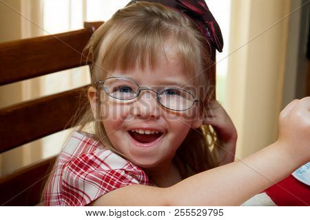 A Young Girl With A Bright Smile And Crooked, Thick Glasses.  Her Eye Has Strabismus From Ocular Pal