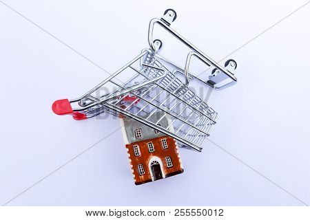 Housing Market Concept - Miniature Supermarket Trolley Tipped Over With A Miniature House Inside.