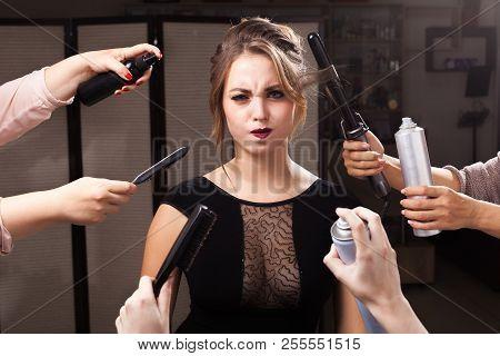 beautiful wriggling model is surrounded by many hands holding hair curler, sprays and brushes.. concept of professional makeup products poster