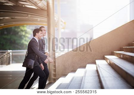 Two American Businessmen Are Discussing Their Work While Walking Up The Stairs.