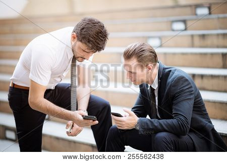 Business Partners  Talking About New Project In The City On Break. They Are Use Smartphone Discussin