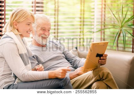Lovely Senior Couple Holding An Old Photograph,when They Were Young While Sitting On Couch At Home S