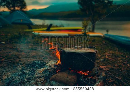 Camp And Cooking In Field Conditions, Boiling Pot At The Campfire On Picnic In Morning.  Cooking Din