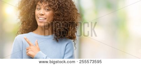 African american woman wearing a sweater cheerful with a smile of face pointing with hand and finger up to the side with happy and natural expression on face looking at the camera.