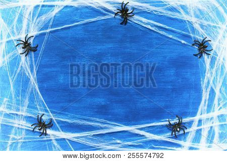 Halloween Background. Spider Web And Spiders As The Symbols Of Halloween On The Dark Blue Wooden Bac