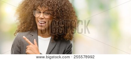 African american business woman wearing glasses cheerful with a smile of face pointing with hand and finger up to the side with happy and natural expression on face looking at the camera.