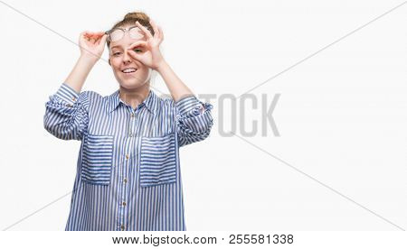 Young blonde business woman doing ok gesture with hand smiling, eye looking through fingers with happy face.