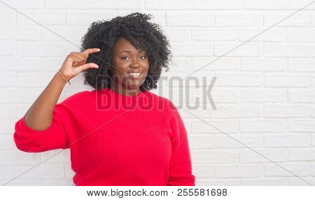 Young african american plus size woman over white brick wall smiling and confident gesturing with hand doing size sign with fingers while looking and the camera. Measure concept.