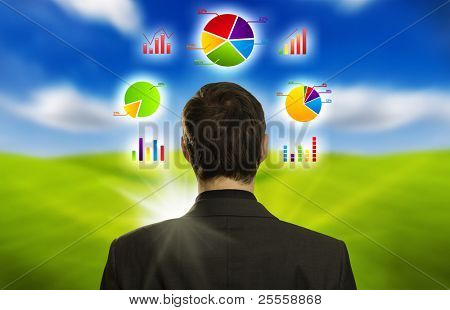 Young businessman with pie charts floating around his head