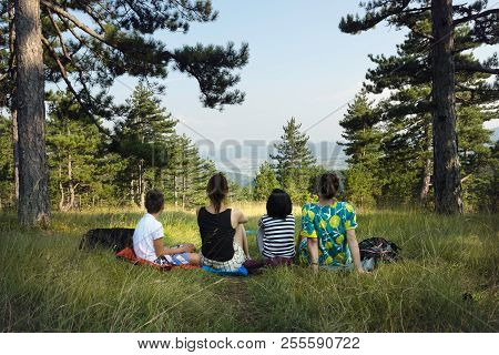 Family Hiking In Nature. Two Women Relaxes With Kids After A Walk In Nature. Family Enjoy Nature In