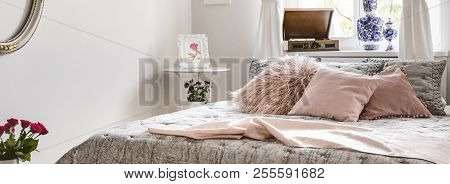 Panorama Of Pink Pillows And Blanket On Bed In Bedroom Interior In English Style With Flowers. Real