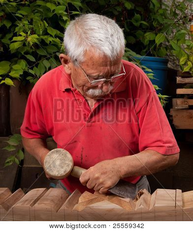 Old woodcarver working with mallet and chisel 10
