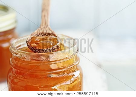 Front View Of The Tip Of A Wooden Spoon Full Of Homemade Cantaloupe Jam Resting On An Open Jar Fille