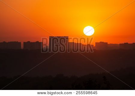 Dawn Sun On The Background Of Distant Buildings. The Red Dawn Sky And The Fireball Of The Sun. Beaut