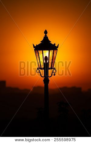 The Dawn Sun Shining Through The Lantern. Dawn Dawn And An Old Lantern In The Background