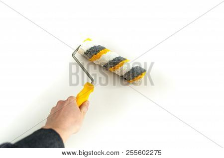 Close Up Of Painter Arm Painting A Wall With Paint Roller. Hand With Paintbrush Roller Isolated On W
