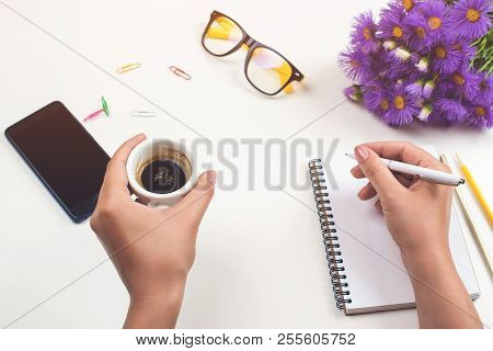 Woman's Hands With Coffee On Office Desk. Workplace With Notebook, Phone, Glasses, Pen, Lilac Flower