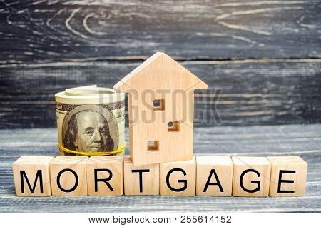 Wooden House And Dollars. Wooden Blocks And The Inscription