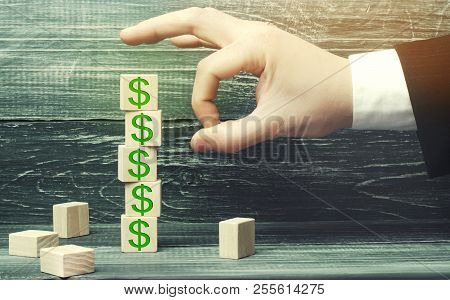 Businessman Removes A Cube With A Picture Of Dollars. Financial And Economic Crisis. Capital Outflow