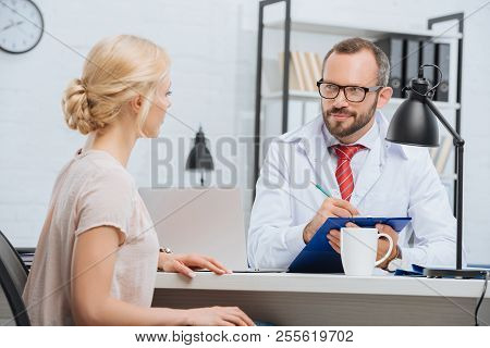 chiropractic in white coat making notes in notepad with female patient near by at table during appointment in clinic poster