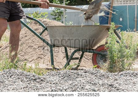 Worker Use The Shovel And Fill The Wheelbarrow With Construction Waste. Construction Tools. Worker W