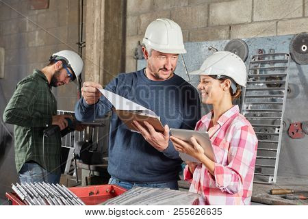 Young woman as apprenticeship trainee with blue collar worker instructor