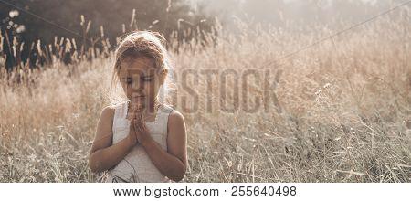 Little Girl Closed Her Eyes, Praying Outdoors, Hands Folded In Prayer Concept For Faith, Spiritualit