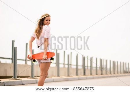 Portrait of Young Beautiful Smiling Blonde Girl with Orange Skateboard on the Bridge