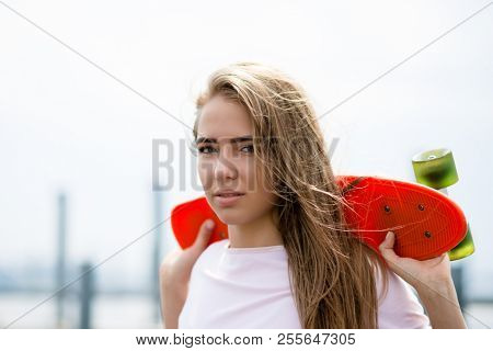 Portrait of Young Beautiful Blonde Girl with Orange Skateboard on the Bridge