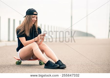 Portrait of Young Beautiful Smiling Blonde Girl Using Smartphone while Sitting on the Skateboard on the Bridge