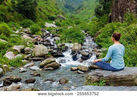 Woman in Hatha yoga asana Padmasana outdoors at tropical waterfall