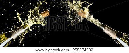 Celebration Theme With Explosion Of Splashing Champagne Sparkling Wine Bottles On Black Background