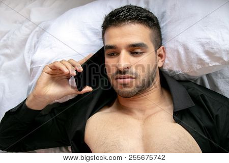 Handsome Man With Open Black Shirt Lies In Bed Using Mobile Cell Phone