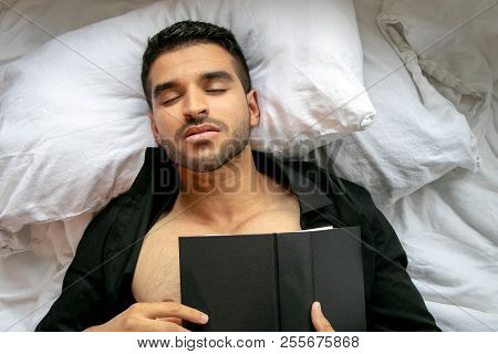 Man In Bed With Open Shirt And Pecs Sleeps Reading Hardback Book