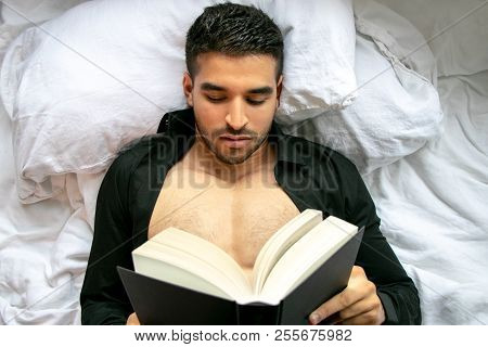 Man In Bed With Open Shirt And Pecs Reading Hardback Book