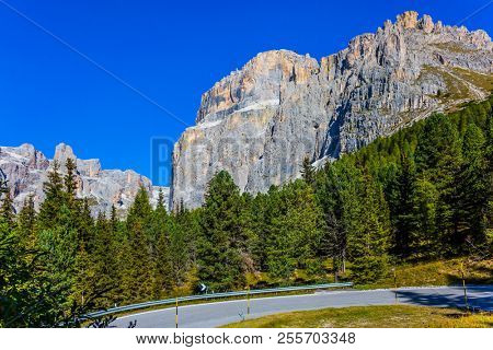 Dolomite Alps. The beautiful sunny day. The road passes in the coniferous forests at the foot of limestone and dolomite rocks. The concept of active, extreme and automobile tourism