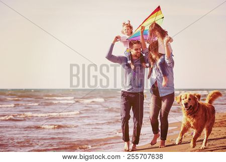 happy young family with kids having fun with a dog and  kite at beach during autumn day filter