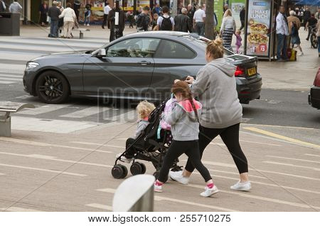 Corby, United Kingdom - August 28, 2018: Young Mother Walking In Street With Two Childrens And Pushc