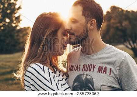 Young Couple In Love Outdoor. They Are Smiling And Looking At Each Other. Close Up Romantic Beauty P
