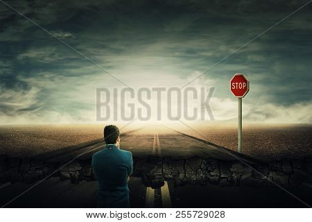 Surreal View As A Man Stand On A Crushing Asphalt Road And A Stop Red Sign In Front. Deep Hole In Th