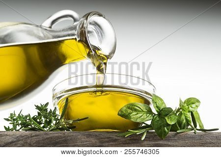 Bottle Of Virgin Olive Oil And Herbs Pouring In A Bowl Close Up