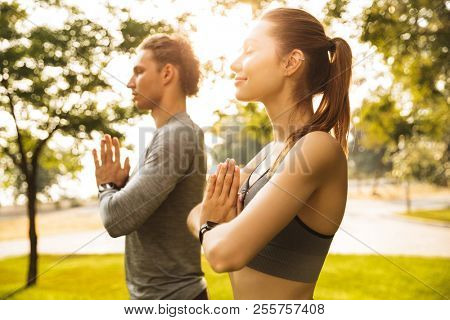 Image of athletic sporty couple man and woman 20s in tracksuits holding palms together while working out or doing yoga in green park