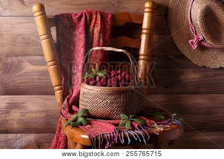 Fresh Raspberries In A Wicker Basket On The Chair