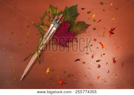 Paint Brushes And Autumnal Leaves On Wooden Background