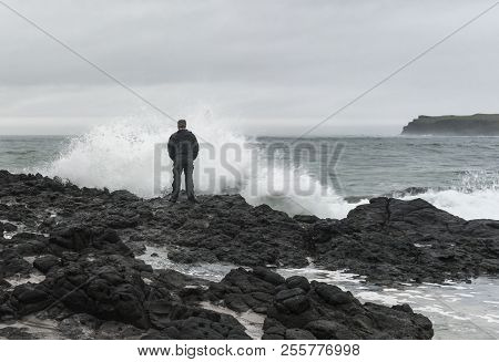 A Man Standing On Rocks In Front Of A High Wave.