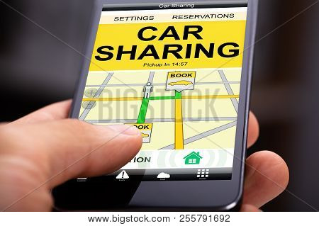 Person Using Car Sharing Application On Cell Phone
