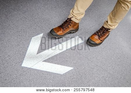Male Feet With Casual Shoes Stepping Over Light Arrowhead Go Forward Sign On The Floor. Keep Moving